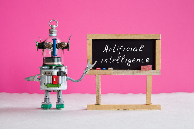 Artificial Intelligence And Machine Learning Cocnept. Funny Robotic Futuristic Character, Black Chalkboard With Handwritten Text Artificial Intelligence. Pink Background